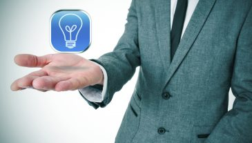 man wearing a suit with an icon with a light bulb in his hand