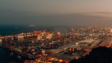 A distant shot of a port with boats loaded with cargo and shipment during nighttime
