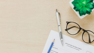 Top view business office desk background.The applying for a job form and pen pencil eyeglasses tree on wooden table background with copy space.