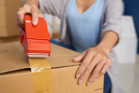 Close-up view of unrecognizable woman sealing cardboard box with adhesive tape while preparing for moving out
