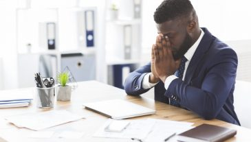 Young tired african american businessman having stress at work, sitting with closed eyes at workplace, empty space